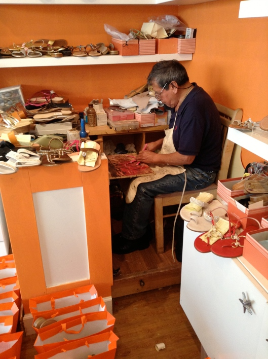 A neopolitan craftsman works on a pair of sandals in the shop.
